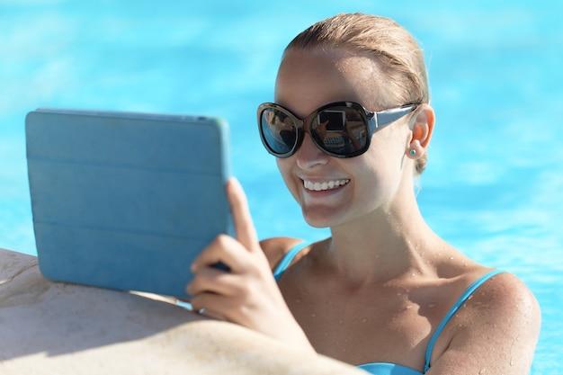 Junge frau in einem pool unter verwendung des tablet-computers Premium Fotos