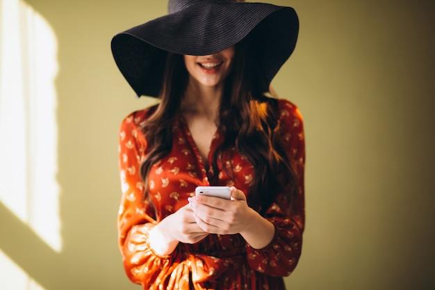 Junge frau in einem schönen kleid unter verwendung des telefons und online kaufen Kostenlose Fotos