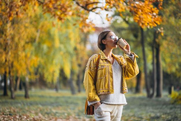 Junge frau in einem trinkenden kaffee des herbstparks Kostenlose Fotos