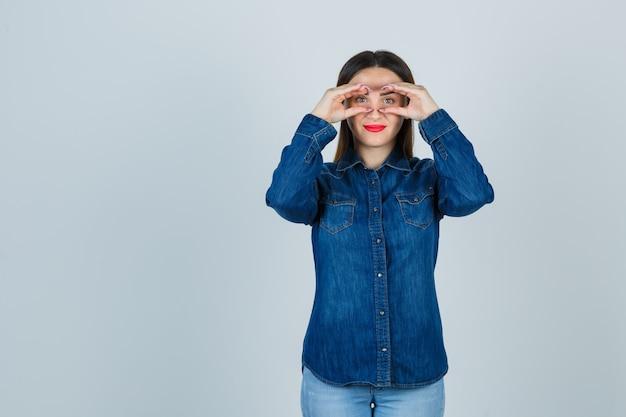 Junge frau in jeanshemd und jeans, die vorgibt, durch fernglas zu spähen und fröhlich auszusehen Kostenlose Fotos