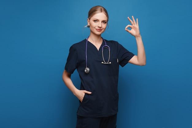 Junge frau in medizinischer uniform und mit stethoskop, das ok-geste zeigt Premium Fotos