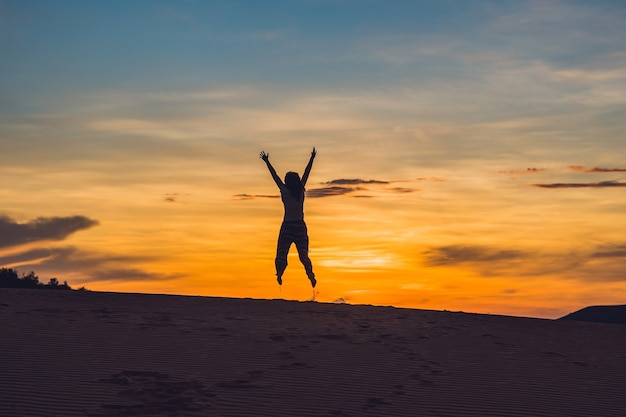 Junge frau in rad sandiger wüste bei sonnenuntergang oder morgengrauen Premium Fotos