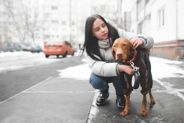 Junge frau in warmen kleidern sitzt mit einem hund auf dem boden und passt das halsband an Premium Fotos