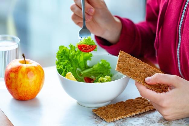 Junge frau isst einen gesunden, frischen gemüsesalat mit knusprigem roggenbrot. diät und gesunder lebensstil konzept. diätessen. richtige ernährung und richtig essen Premium Fotos