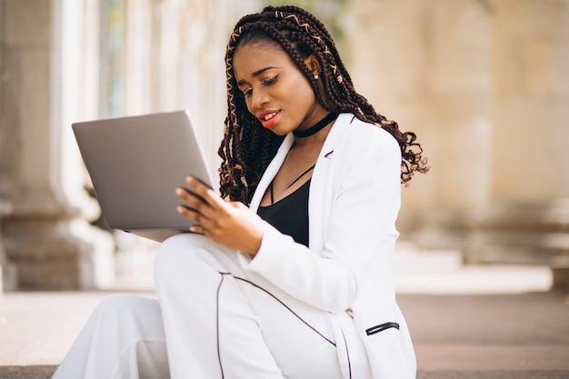 Junge frau kleidete im weiß unter verwendung des laptops an Kostenlose Fotos