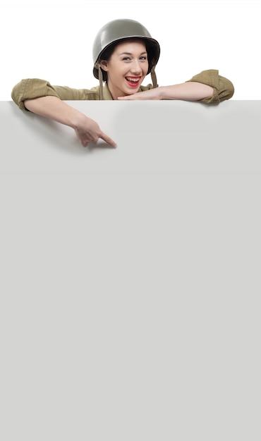 Junge frau kleidete in der amerikanischen militäruniform ww2 an, die schild mit kopienraum zeigt Premium Fotos