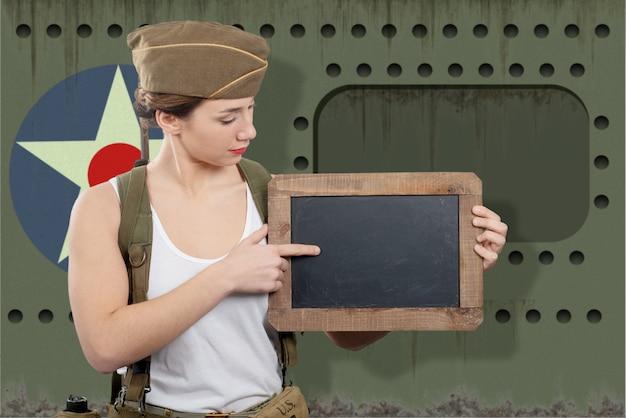 Junge frau kleidete in der wwii-militäruniform mit der kappe an, die leere leere tafel mit einem kopienraum zeigt Premium Fotos