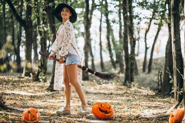 Junge frau kleidete in welchem hut mit besen auf halloween im wald an Kostenlose Fotos