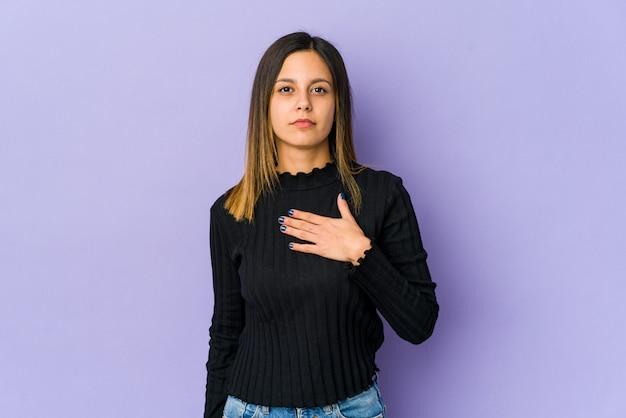Junge frau lokalisiert auf purpur, der einen eid leistet und hand auf brust legt. Premium Fotos