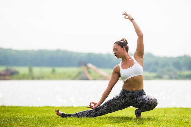 Junge frau machen yoga-pose am park am morgen mit sonnenlicht Kostenlose Fotos