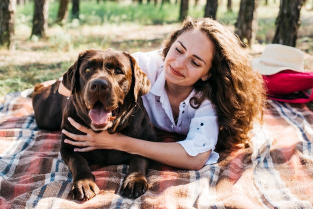Junge frau macht ein picknick mit ihrem hund Kostenlose Fotos