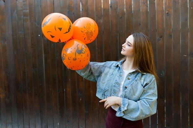 Junge frau mit aufblasbaren orange ballons halloweens auf braunem hintergrund Premium Fotos