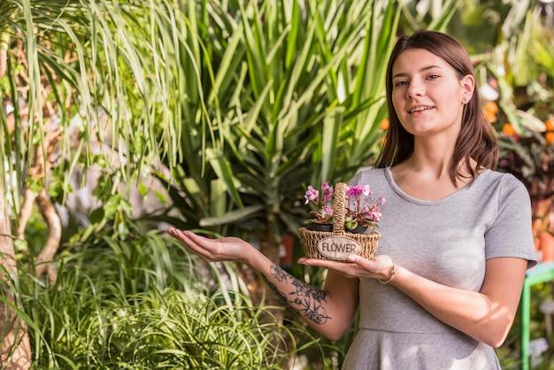 Junge frau mit blumen im korb nahe grünpflanzen Kostenlose Fotos