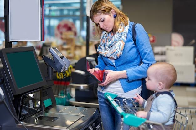 Junge frau mit dem baby, das mit selbstkasse zahlt Premium Fotos