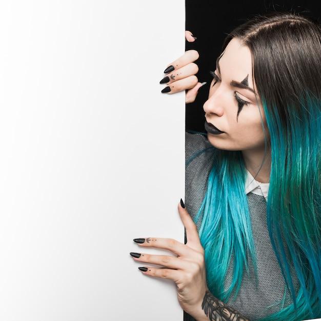 Junge frau mit dem blauen haar, das weißes brett betrachtet Kostenlose Fotos