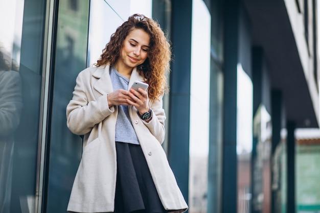 Junge frau mit dem gelockten haar unter verwendung des telefons an der straße Kostenlose Fotos