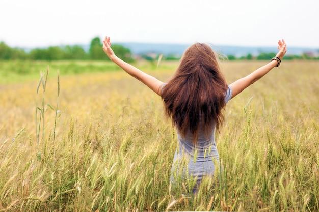Junge frau mit dem langen braunen haar, das auf dem weizengebiet steht Premium Fotos