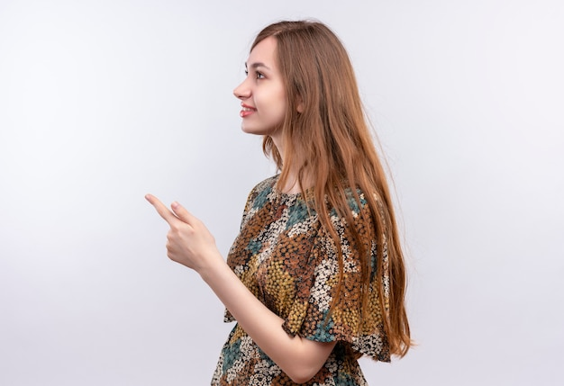 Junge frau mit dem langen haar, das buntes kleid trägt, das seitlich steht und mit dem finger zur seite steht, die über weißer wand steht Kostenlose Fotos