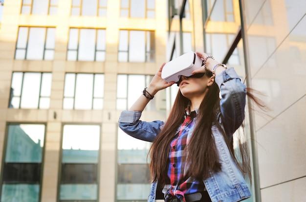 Junge frau mit dem langen haar in vr-gläsern auf modernem glasgebäude Premium Fotos