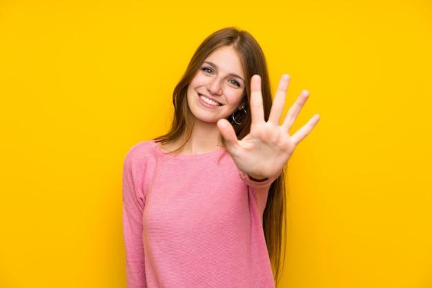 Junge frau mit dem langen haar über der lokalisierten gelben wand, die fünf mit den fingern zählt Premium Fotos