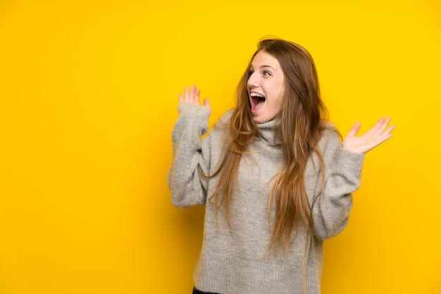 Junge frau mit dem langen haar über gelbem hintergrund mit überraschungsgesichtsausdruck Premium Fotos