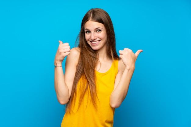 Junge frau mit dem langen haar über lokalisierter blauer wand mit den daumen up geste und lächeln Premium Fotos