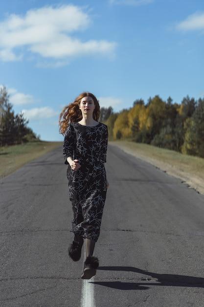 Junge frau mit dem langen roten haar in einem leinenkleid in einem natürlichen standort auf dem hintergrund Kostenlose Fotos