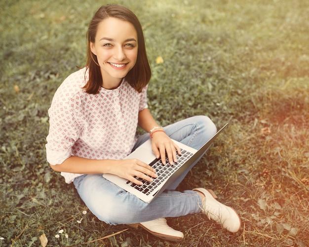 Junge frau mit dem laptop, der auf grünem gras sitzt Kostenlose Fotos