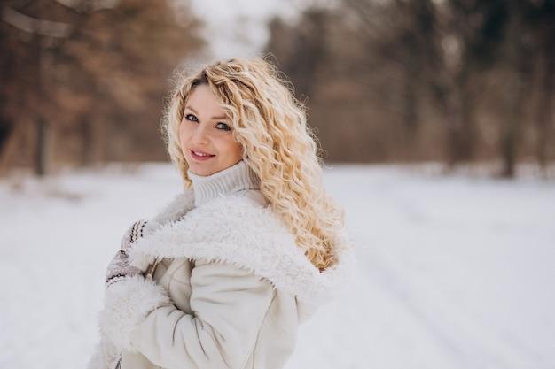 Junge frau mit dem lockigen haar, das in einem winterpark geht Kostenlose Fotos