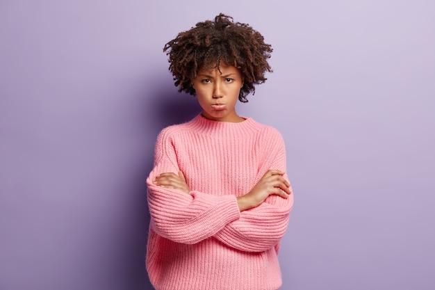 Junge frau mit dem lockigen haar, das rosa pullover trägt Kostenlose Fotos
