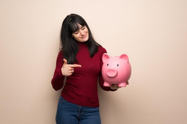 Junge frau mit dem roten rollkragenpullover, der ein sparschwein hält Premium Fotos