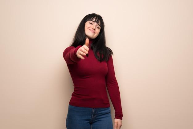 Junge frau mit dem roten rollkragenpullover, der hände für das schließen viel rüttelt Premium Fotos