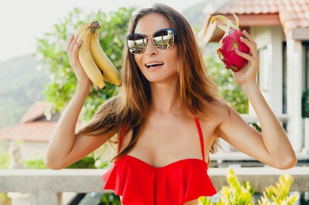 Junge frau mit dem schönen schlanken körper, der mit tropischen früchten aufwirft, die roten badeanzug des bikinis auf tropischem villenresort im urlaub in asien tragen, dünne figur, sommerarttrend, gesunde lebensstildiät Kostenlose Fotos