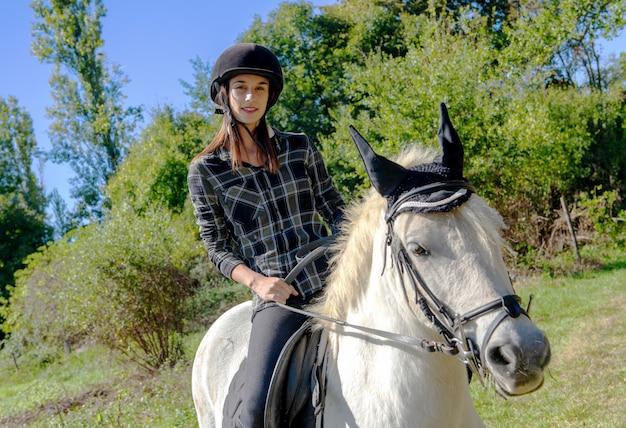 Junge frau mit dem schwarzen sturzhelm, der weißes pferd reitet Premium Fotos