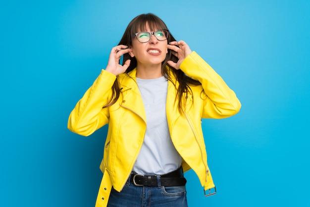 Junge frau mit den ohren der gelben jackenbedeckung mit den händen. frustrierter ausdruck Premium Fotos