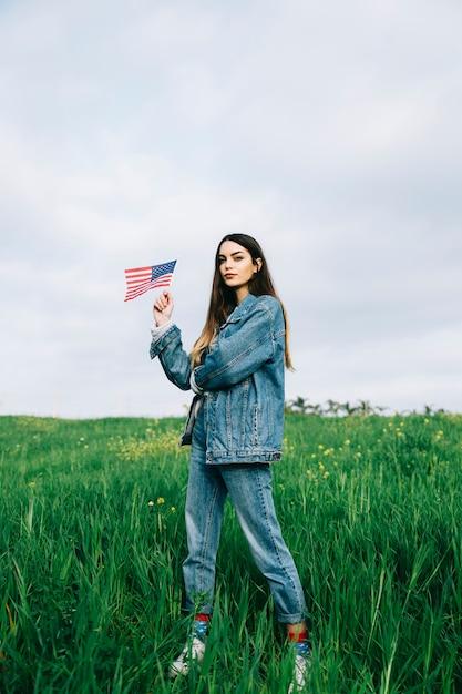 Junge frau mit der amerikanischen flagge, die auf dem gebiet bleibt Kostenlose Fotos