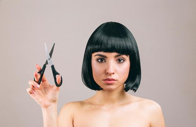 Junge frau mit der aufstellung des schwarzen haares. ich schaue gerade. schere in der hand halten. ernster brunette mit pendelhaarschnitt. Premium Fotos
