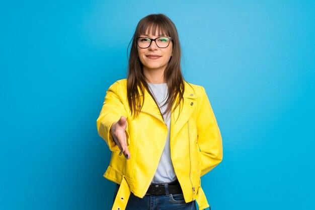 Junge frau mit der gelben jacke, die hände für das schließen viel rüttelt Premium Fotos