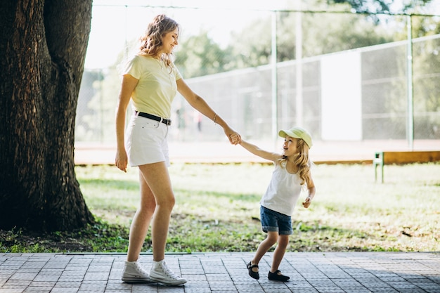 Junge frau mit der kleinen tochter, die in park geht Kostenlose Fotos