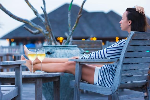 Junge frau mit einem glas weißwein am abend Premium Fotos