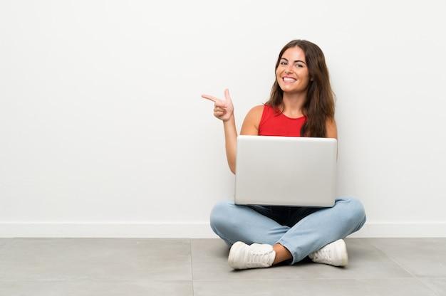 Junge frau mit einem laptop, der auf dem boden zeigt finger auf die seite sitzt Premium Fotos