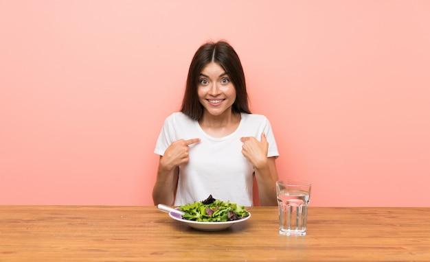 Junge frau mit einem salat mit überraschungsgesichtsausdruck Premium Fotos