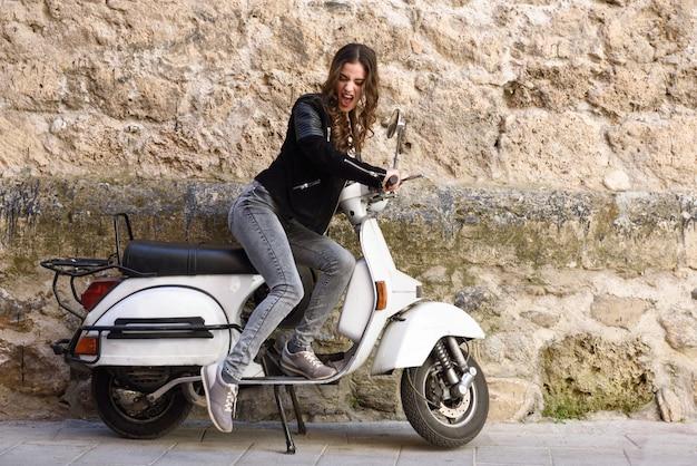 Junge frau mit einem vintage-motorrad spielen   Kostenlose