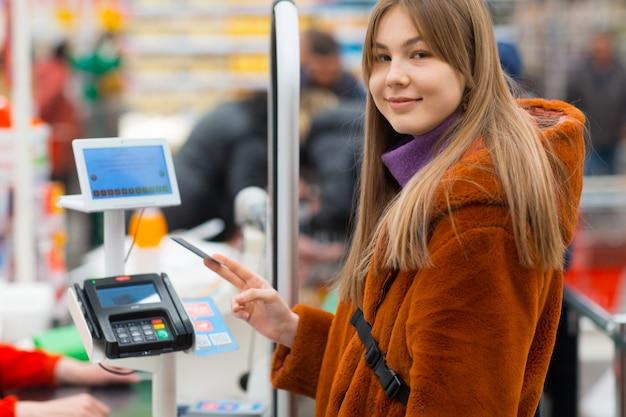 Junge frau mit einer kreditkarte zahlt für einkäufe an der kasse im laden Premium Fotos