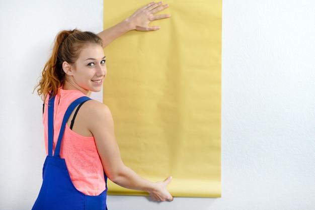 Junge frau mit einer rolle der gelben tapete Premium Fotos
