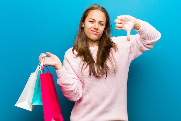 Junge frau mit einkaufstaschenblauwand Premium Fotos