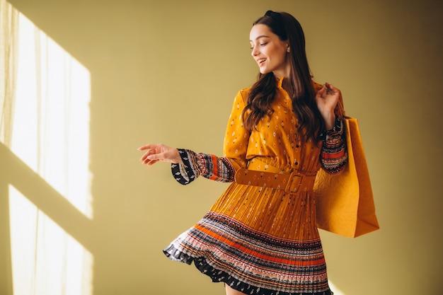 Junge frau mit einkaufstüten in einem schönen kleid Kostenlose Fotos