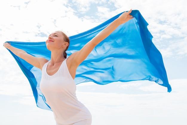 Junge frau mit fliegenden blauen schal Kostenlose Fotos