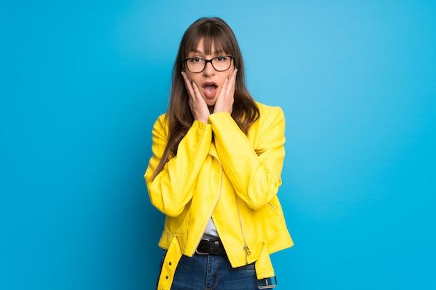 Junge frau mit gelber jacke auf blauem hintergrund beim schauen überrascht und entsetzt Premium Fotos