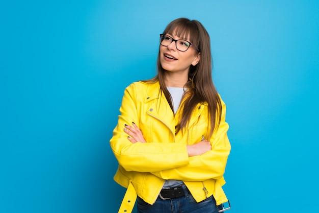 Junge frau mit gelber jacke auf dem blauen hintergrund, der die arme beim lächeln gekreuzt hält Premium Fotos